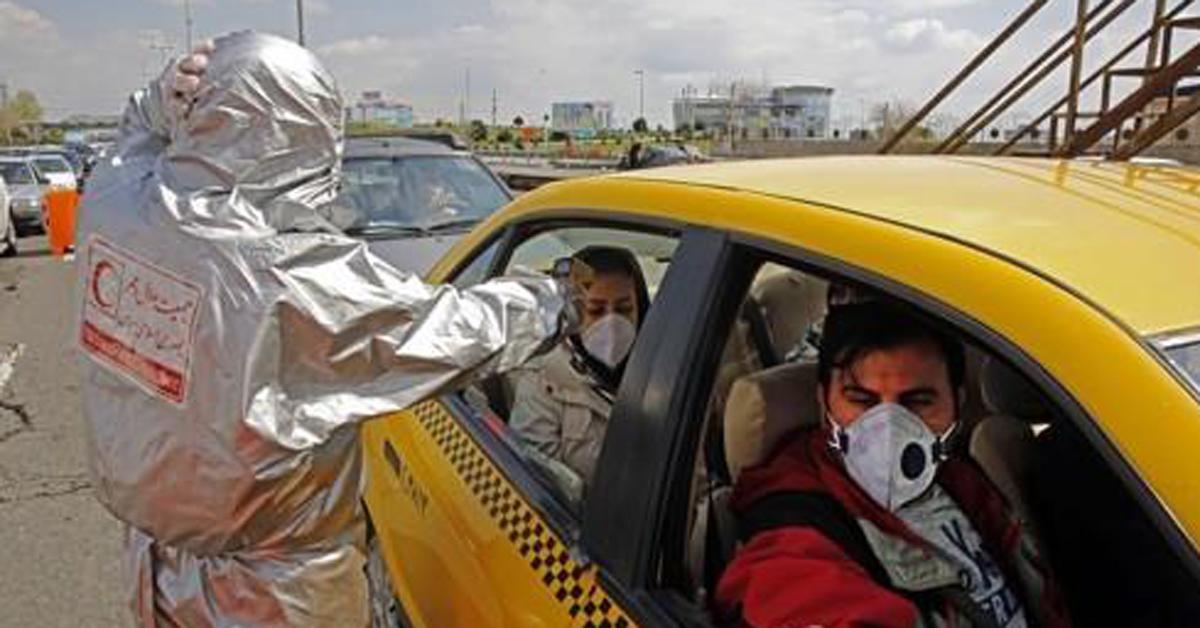 택시에 탄 시민의 체온을 재는 이란 적신월사 직원. AFP=연합뉴스