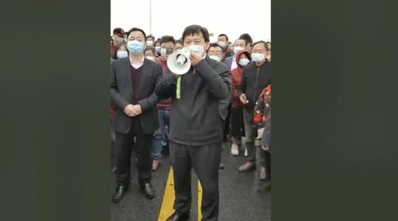 27일 후베이성 황메이현과 장시성 지우장시를 잇는 다리에서 경찰차를 뒤엎는 등 폭동에 준하는 군중 시위가 벌어지자 한 관리가 나와 안정을 호소하고 있다. [중국 신경보망]