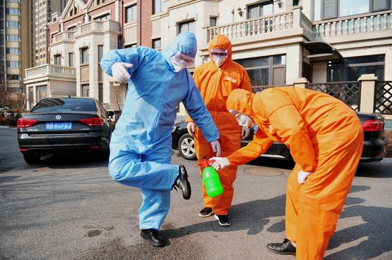 중국 칭다오에서 방역 작업중인 이들이 신발을 소독하고 있다. [EPA=연합뉴스]
