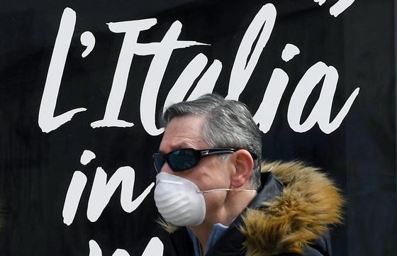 마스크를 착용한 남성이 전국 봉쇄조치가 내려진 지난 27일 밀라노 중심가를 지나가고 있다. EPA=연합