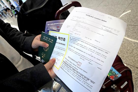 정부는 신종 코로나바이러스 감염증(코로나19)의 해외유입 차단을 강화했다. 해외에서 입국한 내국인이 격리통지서와 검역 확인증을 내보이고 있다. 연합뉴스