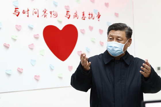 중국에서 코로나19가 기승을 부리던 지난 2월 10일 베이징의 질병예방통제센터를 찾은 시진핑 국가주석이 하트와 함께 '시간에 대항하여 달리고 바이러스에 대항해 싸워라'는 구호가 적힌 벽 앞에서 연설하고 있다. 신화=연합뉴스