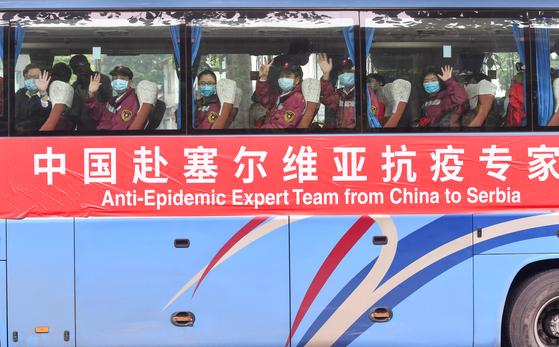 지난 21일 의료와 방역물자를 들고 세르비아의 수도 베오그라드에 도착한 중국 의료지원단이 버스를 타고 이동하고 있다. 신화=연합뉴스
