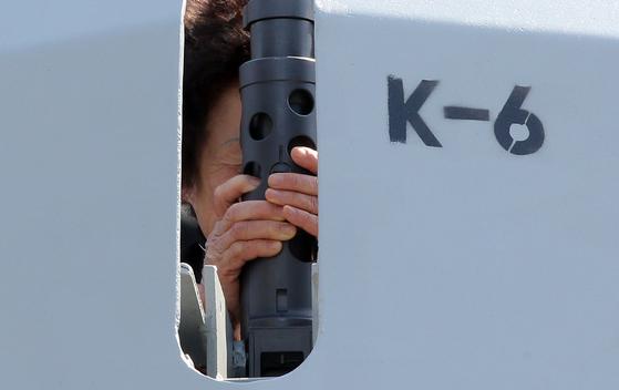 천안함 용사 고 민평기 상사의 어머니 윤청자 여사가 2011년 3월 25일 '3.26 기관총' 기증식에서 해군 영주함에 설치된 '3.26 기관총'을 붙잡고 오열하고 있다. 해군은 윤여사의 기탁금 1억898만8000원으로 이들 K-6 기관총을 도입한 뒤 천안함 용사를 기리기 위해 천안함 폭침일인 3월 26일을 따 이를 '3·26 기관총'이라고 명명했다. [중앙포토]