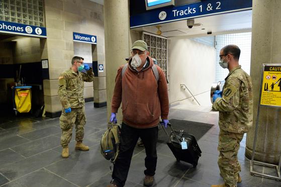 마스크와 장갑을 낀 남성이 30일 미국 로드아일랜드의 한 기차역에서 주방위군 앞을 지나고 있다. 주 방위군은 로드아일랜드주에 도착하는 모든 여행객은 14일간 자가 격리 해야 한다고 안내하고 있다. [AFP=연합뉴스]