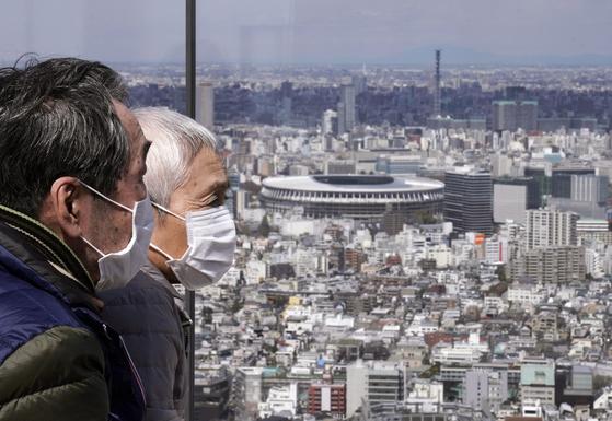지난 24일 마스크를 착용한 노부부 오른쪽으로 도쿄 올림픽과 패럴림픽의 주 경기장이 보인다. [EPA=연합뉴스]