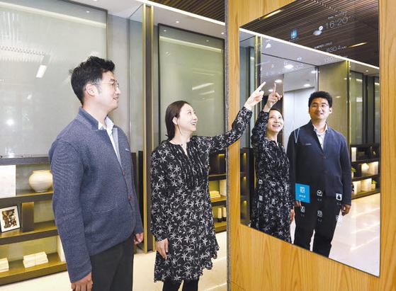 삼성물산 관계자가 음성인식 기능을 활용해 거실 조명과 커튼, 에어컨을 작동하는 모습을 보여주고 있다.