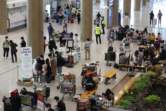 외국에서 국내로 들어오는 모든 입국자들에게 2주간 자가격리 의무화를 시작한 1일 오전 인천국제공항 1터미널에서 인천국제공항공사 직원과 각 시도 관계자들이 해외입국자 전용버스를 안내하고 있다. 해외입국자는 모두 반드시 공항에서 바로 귀가해야 한다. 정부는 이들이 승용차를 이용하도록 적극적으로 권장하되, 승용차 이용이 어려운 경우에는 해외 입국자만 탑승하는 공항버스와 KTX 전용칸을 이용해 수송한다. 연합뉴스