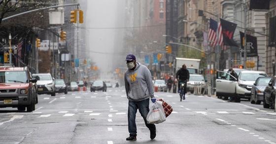 29일 뉴욕 맨해튼에서 한 남성이 마스크를 쓴 채 거리를 걷고 있다. AP=뉴시스
