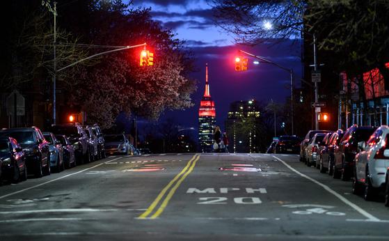 미국 뉴욕 맨해튼 엠파이어 스테이트 빌딩이 코로나19와 사투를 벌이는 의료진을 기리기 위해 붉은색과 흰색 불을 밝혔다. 뉴욕주는 자택 대기 명령을 실시중이어서 행인과 차량을 찾아볼 수 없다. [AFP=연합뉴스]