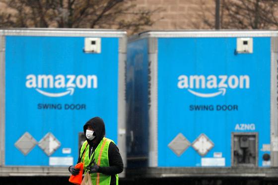 코로나바이러스가 확산 되던 지난 3월 미국 뉴욕 소재 아마존 직원이 트럭 앞을 지나고 있다. [로이터=연합뉴스]