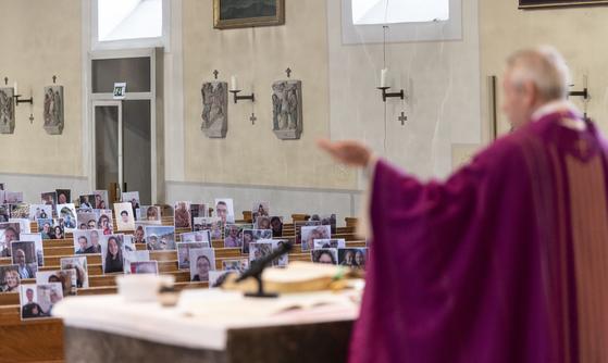 지난 29일 독일 아헤른 교구교회에서 호아킴 지에슬러 신부가 신도들의 사진이 놓여진 성당 앞 연단에서 미사를 진행하고 있다. [AP=연합뉴스]