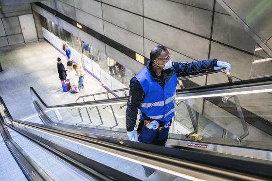 코로나 바이러스 확산을 막기 위해 덴마크 코펜하겐 지하철 역에서 에스컬레이터 핸들을 청소하고 소독하는 작업자. AP=연합뉴스