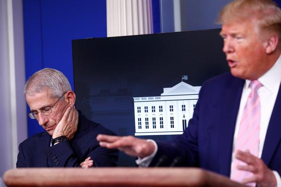 지난 1일(현지시간) 미국 백악관에서 열린 코로나19 브리핑에서 앤서니 파우치 미 국립알레르기감염병연구소장(왼쪽)이 도널드 트럼프 미국 대통령 발언을 듣고 있다. [로이터=연합뉴스]