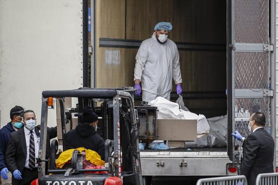 뉴욕 브루클린 병원에서 직원들이 지게차를 동원해 플라스틱 백에 담긴 신종 코로나 희생자의 시신을 임시 시체안치실로 사용하는 냉동 트레일러에 옮겨 싣고 있다.[AP=연합뉴스]