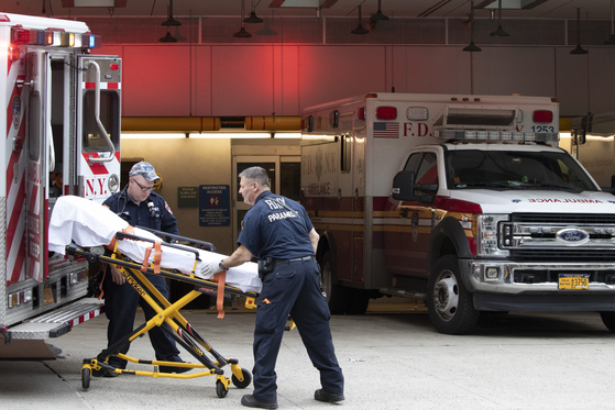 뉴욕 맨해튼에서 구급대원들이 환자를 구급차에 싣고 있다. AP=연합뉴스