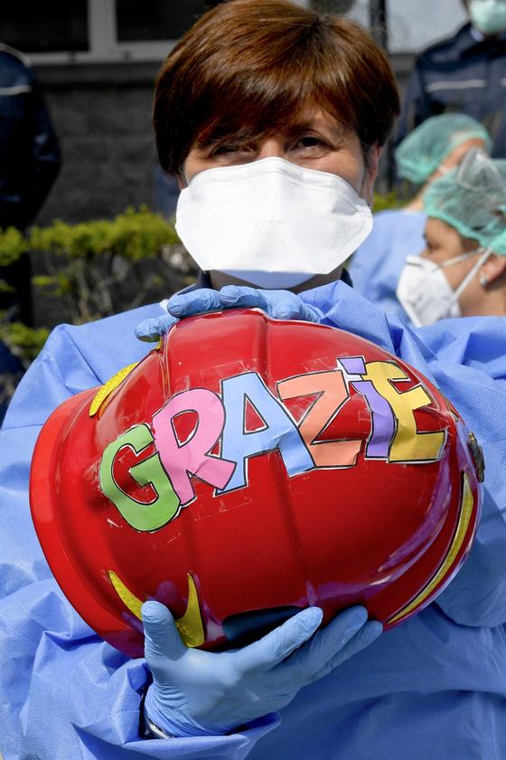 신종 코로나로 인한 피해가 막심한 이탈리아에서 의료진 중 한 명이 선물 받은 헬멧을 들어보이고 있다. '그라찌에(감사합니다)'라고 쓰여있다. [EPA=연합뉴스]