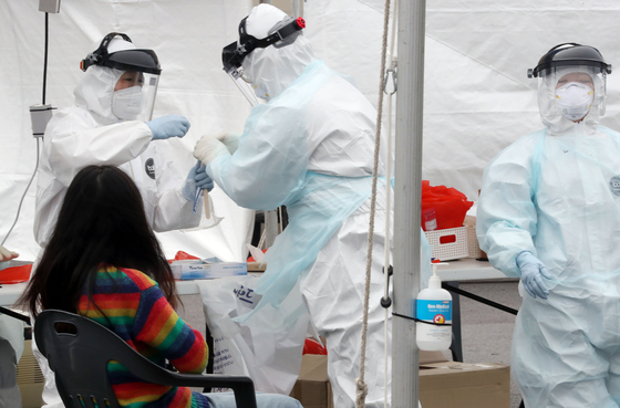 제주국제공항 워킹 스루 진료소(개방형 선별진료소)에서 신종 코로나바이러스 감염증(코로나19) 검사 대상자가 검체 검사를 받고 있다. 뉴스1