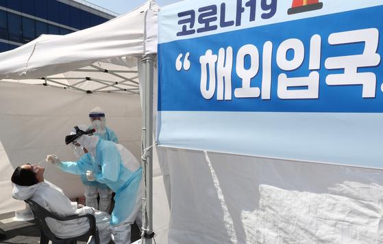 신종 코로나바이러스 감염증(코로나19) 국내 확진자가 1만명을 돌파한 3일 오후 대전 동구 대전역 동광장에 설치된 해외입국자 선별진료소에서 방역관계자가 해외입국자의 검체채취를 하고 있다. [뉴스1]
