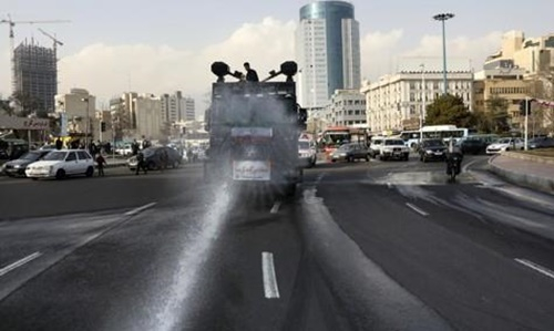 이란 테헤란 시내 도로를 경찰 살수차가 소독하고 있다. AP=연합뉴스