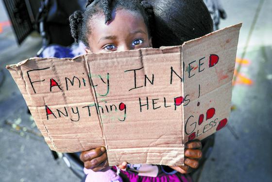 지난달 25일 미국 뉴올리언스의 한 거리에서 세 살짜리 여자아이가 '곤궁한 가족에겐 무엇이든 도움이 돼요'라고 쓴 팻말을 들고 있다. [AP=연합뉴스]