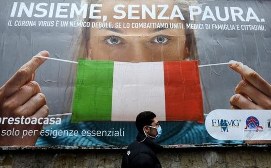 이탈리아 나폴리 거리에서 지난달 22일 이탈리아 국기를 신종 코로나바이러스 감염증(코로나19) 예방 마스크로 표현한 대형 포스터 앞으로 한 남성이 지나고 있다. AFP=연합뉴스