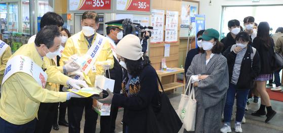 송하진 전북지사가 지난 1일 전주역에서 방역 당국 관계자들과 함께 승객들에게 개인 방역 물품을 나눠주며 신종 코로나바이러스 감염증 확산 방지를 위한 사회적 거리두기에 동참해 줄 것을 호소하고 있다. 뉴스1