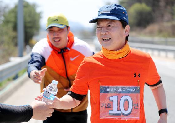 안철수 국민의당 대표가 전날인 5일 오후 전북 임실군에서 국도 17호선을 따라 달리던 중 지지자에게 물병을 받아들고 있다. 연합뉴스