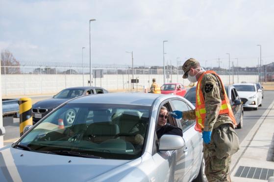 평택 주한미군기지 캠프 험프리에서 코로나19 예방을 위해 군 관계자들이 출입 운전자들을 대상으로 발열 검사를 하고 있다. 연합뉴스