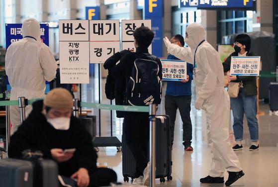 지난달 30일 인천국제공항에서 관계자들이 코로나19 무증상 입국자들을 전용 공항버스로 안내하고 있다. 뉴스1
