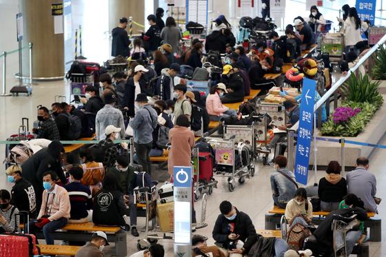해외 입국자들의 신종코로나바이러스 감염증(코로나19) 확진이 증가하고 있는 6일 오후 인천국제공항 입국장에서 입국자들이 버스 탑승을 위해 대기하고 있다. 정부는 해외 입국자의 2주간 자가격리 의무화를 어기는 사례가 발생하자, 지난 5일 부터 자가격리 수칙 위반자에 대한 처벌 강도를 1년 이하의 징역 또는 1천만원 이하의 벌금으로 대폭 강화했다.뉴스1