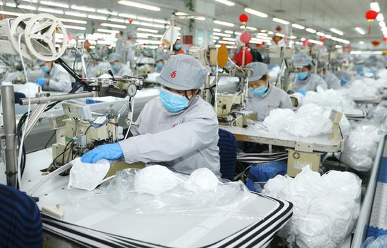 중국 산둥성 칭다오의 한 마스크 공장에서 근로자들이 마스크 생산 작업에 여념이 없다. 그러나 중국 마스크 공장의 60%가 살균 작업장을 갖추지 않은 것으로 폭로돼 충격을 주고 있다. [중국 신화망 캡처]