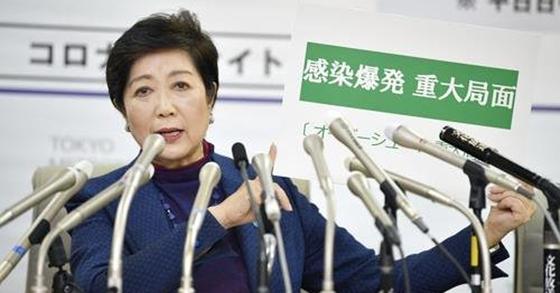 고이케 유리코 일본 도쿄도 지사가 지난달 25일 긴급 기자회견을 하던 중 '감염폭발 중대국면'이라고 쓴 카드를 들어 보이고 있다. [연합뉴스]