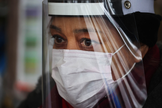 뉴욕의 한 식료품 상점에서 일하는 직원이 마스크 등 보호장구를 쓴 채 일하고 있다. [AFP=연합뉴스]