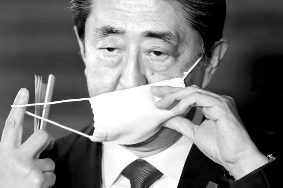 아베 신조 일본 총리가 6일 저녁 기자회견에 앞서 마스크를 벗고 있다. 로이터=연합뉴스