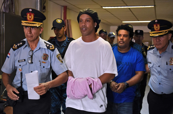 지난달 여권 위조 혐의로 파라과이 경찰에 체포돼 구치소로 향하는 호나우지뉴. [AFP=연합뉴스]