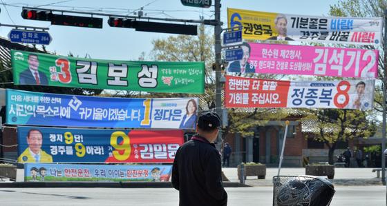 9일 경북 경주역 교차로에서 신호를 기다리는 시민이 지역 국회의원 후보들의 현수막을 지켜보고 있다. 뉴스1