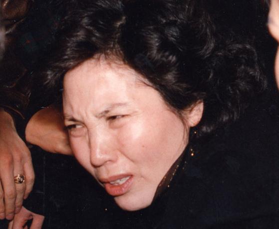 1994년 1월 24일 당시 장영자씨가 기진맥진한 표정으로 서울 구치소로 가기위해 서울지검 직원에 둘러싸여 검찰청사를 나서고 있다. 장씨는 검사가 구속을 통보하자 충격을 받아 한때 실신했었다. [중앙포토]
