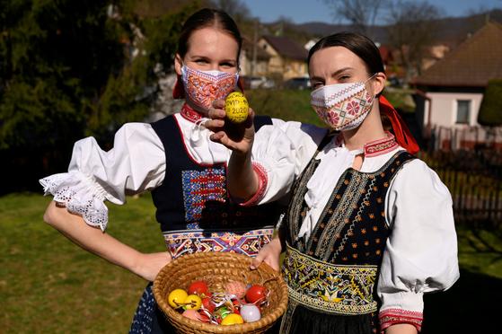 지난 7일 슬로바키아 북서부 소블라호우에서 전통 의상을 입은 두 여성이 마스크른 쓴 채 부활절 달걀을 들어보이고 있다. 달걀에는 신종 코로나바이러스 감염증을 뜻하는 '코비드-19(covid-19) 2020'이란 문구가 들어가 있다. 신종 코로나 사태의 빠른 종식을 기원하기 위해서다. [로이터=연합뉴스]