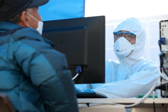 신종 코로나바이러스 감염증(코로나19) 확산이 거듭되는 28일 대구 달서구 계명대학교 동산병원 선별진료소에서 의료진이 코로나19 증상을 호소하며 방문한 시민들에 대해 상담과 검사를 진행하고 있다. 뉴스1