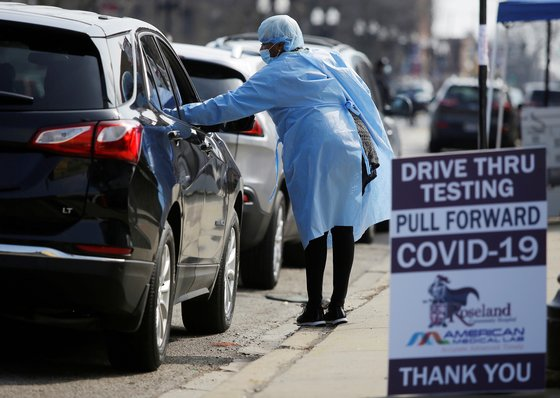 의료진이 미국 시카고에서 신종 코로나 검사를 받기 위해 기다리는 차량 속 운전자와 대화를 나누고 있다. [로이터=연합뉴스]