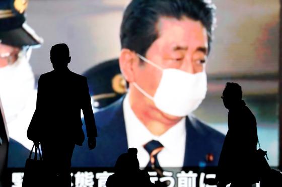 일본 도쿄 거리 대형스크린 앞을 지나는 도쿄 시민들. 로이터=연합뉴스