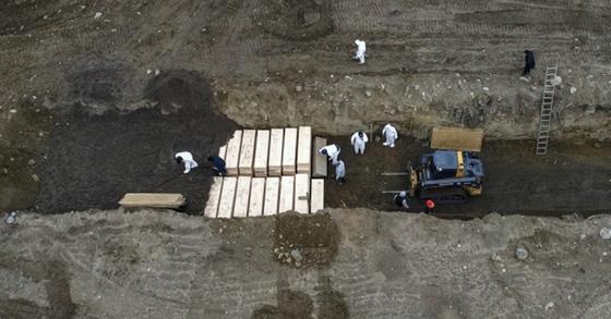 미국 뉴욕시 브롱크스 인근 해역에 있는 하트 섬에서 9일 개인방호장비를 착용한 인부들이 코로나19 사망자들의 시신이 담긴 관들을 파묻고 있다. AP=연합뉴스