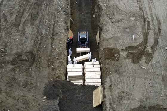 9일 미국 뉴욕 브롱스 앞바다에 있는 하트섬에서 의료용 방호복을 입은 인부들이 큰 구덩이를 파고 신종 코로나 시신 수십구를 임시로 집단 매장하고 있다.[AP=연합뉴스]