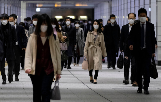 긴급사태선언이 발효된 이후에도 많은 직장인들이 정상 출근을 하고 있다. 사진은 지난 9일 도쿄 신주쿠역을 나서고 있는 출근자들. [AFP=연합뉴스]
