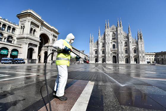 지난달 31일 이탈리아 밀라노 시내 중심가인 두오모 광장에서 보호장구를 착용한 방역요원이 소독약을 뿌리고 있다. 로이터=연합뉴스