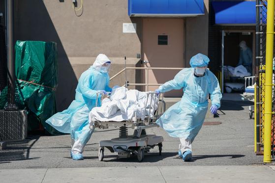 미국 최대 진앙인 뉴욕에서 연일 800명씩 사망자가 발생하는 가운데 뉴욕 브루클린 위코프 병원에서 의료진이 사망자를 임시 안치실로 사용하는 냉동 트레일러로 옮기고 있다.[AFP=연합뉴스]