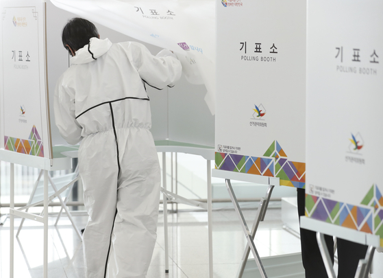 제21대 국회의원 선거 사전투표 첫 날인 10일 인천국제공항 제2터미널 출국장에 설치된 사전투표소에서 방호복을 입은 유권자가 투표를 위해 기표소로 들어가고 있다. 연합뉴스