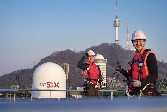 SK텔레콤 직원들이 서울 시내 한 빌딩 위에서 5G 기지국을 점검하며 5G 상용화 1주년을 기념해 포즈를 취하고 있다. / 사진:SK텔레콤