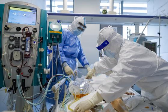 지난 11일 신종 코로나바이러스 감염증(코로나19)의 발원지인 중국 후베이성 우한의 퉁지병원 집중치료실(ICU)에서 방호복 차림의 의료진이 신종 코로나 환자를 치료하고 있다. [신화=연합뉴스]